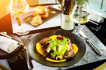 Tasty dish with juicy beef steak and fresh lettuce leaves at a restaurant