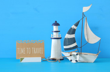 nautical concept image with sail boat, lighthouse and note over blue wooden table and background.