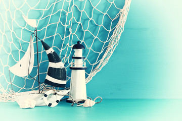 nautical concept with white decorative sail boat, lighthouse, seashells and fishnet over blue wooden table and background.