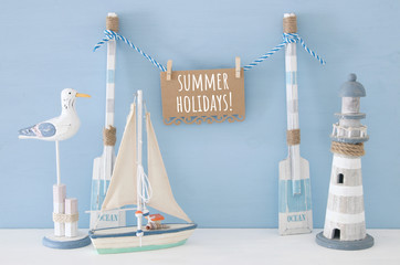 nautical concept with wooden decorative boat oars and hanging note message on a string next to lighthouse, seagull and boat over blue background.