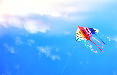 Colorful kite flying in the blue sky through the clouds