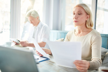Mature blonde reading financial documents while working in cafe on background of colleague