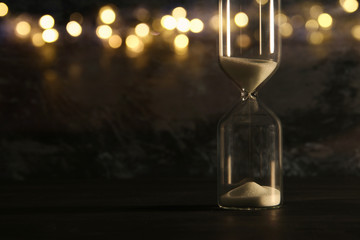 Image of hourglass as time passing concept over black background for business deadline. Glitter overlay.
