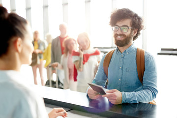 Happy young bearded man in eyeglasses and denim shirt showing his passport to check-in receptionist before flight