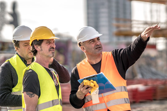 Three civil engineers wearing protective vests and helmets at work on construction site
