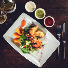 Delicious prepared shrimp with tomatoes, sauce and basil leaves at a restaurant. Top view, flat lay, toned image