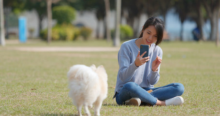 Woman taking photo on her dog with cellphone