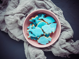 Festive, fragrant biscuits in the form of dolphins and fish, covered with turquoise glaze in a beautiful plate on a dark textured surface Wall mural