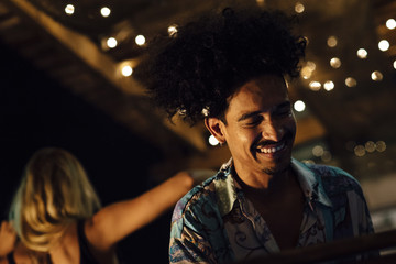 Indian ethnicity DJ laughing during a tropical party in the caribbean in Santa Marta, Colombia