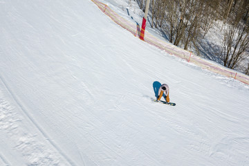Active leisure and winter entertainment. Skiers and snowboarders riding on a ski slope at ski resort. Quadcopter view