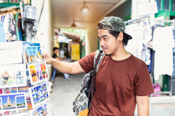 Japanese tourist enjoying sightseeing exploring city and buy postcards at Tha Pae Walking Street, Chiang mai Province, Thailand