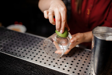 Bartender girl rubbing a glass with lime