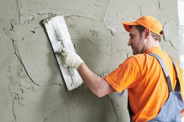 Renovation. Plasterer putting plaster on wall.