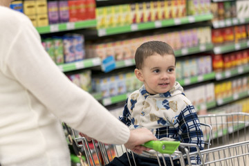 Adorable little boy, sitting in a shopping cart, smiling