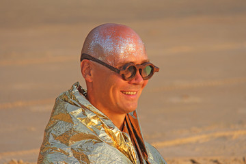 A bald and handsome man freak smiles in a golden cape or clothes