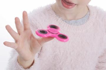 enfant jouant avec jouet de main rotatif rose