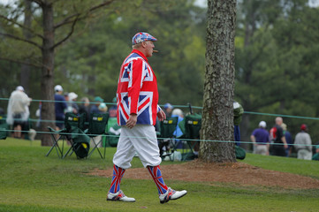 A gold patron smokes a cigar as he walks along the second fairway during third round play of the 2018 Masters golf tournament in Augusta