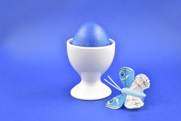 Blue decorated easter egg stock images. Spring decoration images. Ceramic egg stand with blue egg. Easter decoration on a blue background