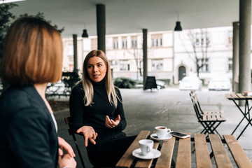 Two young businesswoman talking.