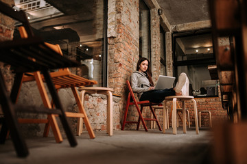 Casual girl relaxing using laptop at terrace with old brick walls.