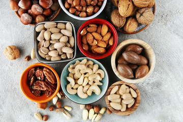 mixed nuts on grey background. Healthy food and snack. Walnut, pecan, almonds, hazelnuts and cashews.