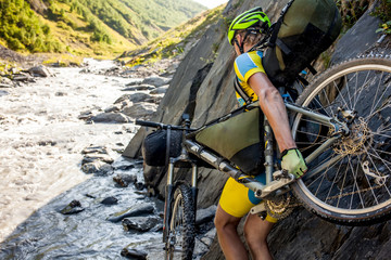 Mountain biker is crossing the river in the highlands of Tusheti region, Georgia