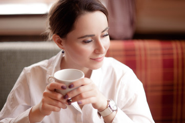 A woman sits at a table in a cafe, drinks tea and enjoys the taste