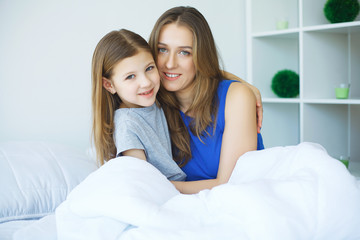 Happy mother and daughter lying in bed