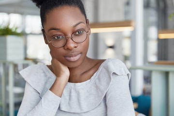 Thoughtful African American woman with dark skin, has full lips, wears round glasses, being deep in thoughts, dreams about good rest, thinks about something. Beautiful pensive female student