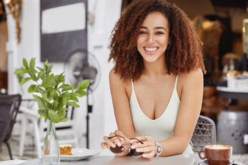 Beautiful African American female with broad pleasant smile rests in sidewalk cafe alone, enjoys good rest during summer vacation, keeps sunglasses in hands and drinks cappuccino with tasty cake
