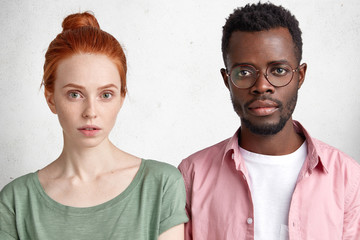 Horizontal shot of confident interracial female and male students meet after classes to prepare project work, look seriously at camera. Attractive redhead freckled woman and her dark skinned boyfriend