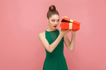 Cunning woman unboxing red gift box looking inside