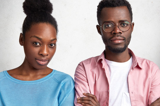 Indoor horizontal shot of confident attractive African American male and female looks with serious expression at camera, meet together to discuss future plans, isolated over white concrete wall