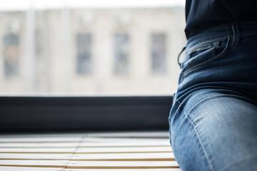 man in blue jeans sitting on the windowsill