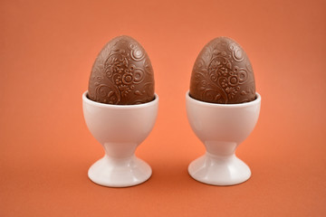 Chocolate egg in an egg holder stock images. Easter egg on a brown background. Breakfast still life. Easter concept. Two chocolate eggs