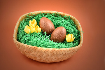 Basket of easter eggs stock images. Chocolate Easter eggs. Easter basket on a brown background. Easter decoration photo. Spring decoration images. Easter concept