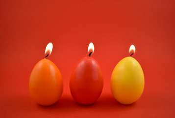 Egg candle stock images. Colored candles on a red background. Colorful Easter candles. Easter concept