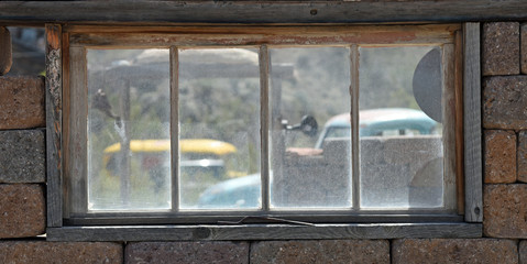 View through an old window to vintage cars