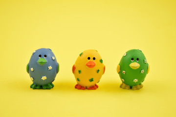 Colorful Easter chickens stock images. Easter decoration on a yellow background. Spring decoration images. Easter concept