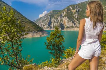 Красивая молодая женщина в белой рубашке и белых шортах стоит спиной на фоне озера Пивское в горах Черногории