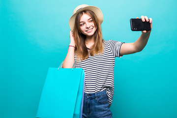 Beautiful girl holding shopping bags and taking selfie with cell phone isolated on green background