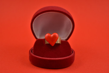 Ring with red heart stock images. Ring in gift box. Propose day concept. Ring of love on a red background