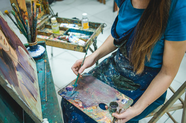 Artist painting a picture in a studio. Closeup view