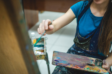 Artist paints on canvas in art studio using easel