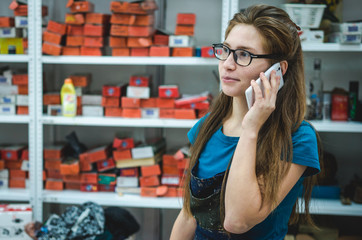 Portrait of pretty girl accepts an order by phone at warehouse