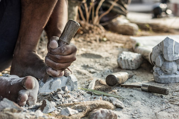 Man barefoot sculpting a rock with a chisel at Chamundi Hills in Mysore, India. Indian sculptor working on street