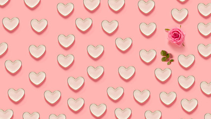 Pink hearts and a rose on a pastel pink background