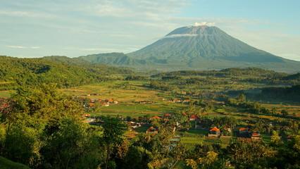 malerischer Vulkan Mt.Agung  hinter grünen Reisfeldern und vereinzelten Häusern