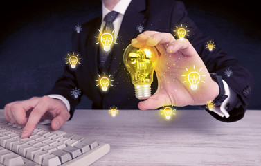 A creative businessman has a bright idea concept with office worker holding light bulb in foreground.
