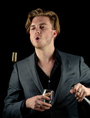 Male model in a classy dark suit isolated against a black background. Model holding a bottle of red wine and spitting the cork out